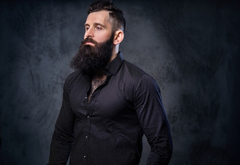 A man in a black shirt with tattoos on his arms.