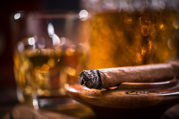Cuban cigar smoking in wooden ashtray