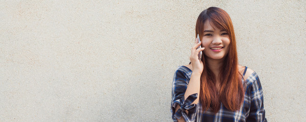 Beautiful asian young woman talking on mobile phone, over concrete wall. Panoramic banner. Vintage tone filter color style.