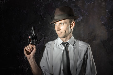 Black and white picture of private detective with gun in both hands. Agent stay front to camera. Criminal scene. Studio shot