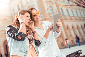 Girls in casual clothes holding a tablet, listening to music.