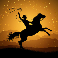 Silhouette of cowboy with lasso on rearing horse