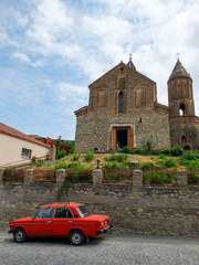 Old red car in front of St. George's Church - Signagi (Georgia)