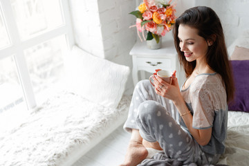 Smiling young woman with cup of aromatic tea at home. Waking up with positive energy charge for whole day, sunrise enjoyment and relaxation, refreshment drink concept