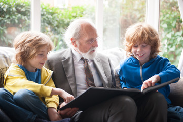grandfather and grandsons looking at family album