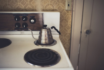 A vintage stove by an orange wall with a modern coffeepot
