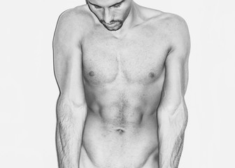 handsome man body on a white wall,gym, exercise, sex,direct light