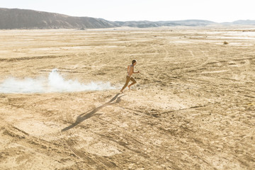 A young man running shirtless in the desert