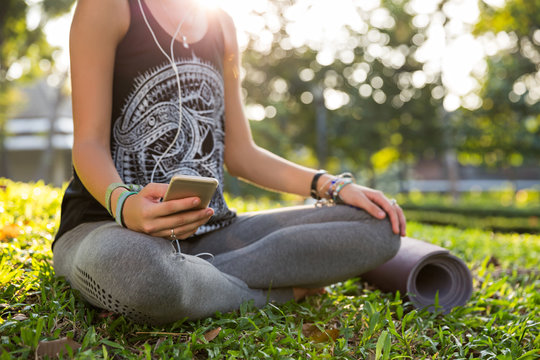 Closeup of a young woman listening to music while sitting in a park