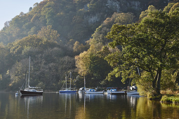 Boats and autumnal colour. Ullswater, Cumbria, UK.