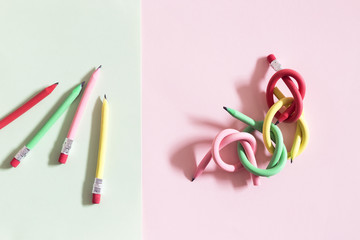 Individual and linked flexible pencils arranged on colorful paper