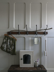 Interior of a Hipster Vintage decorated bathroom in England with wood panelled wall and coat hooks