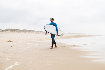 Young male surfer wearing wetsuit