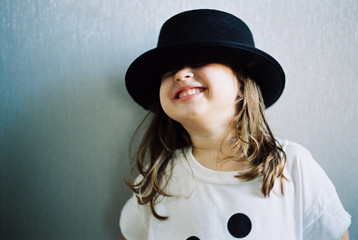 Beautiful young girl in an over sized t shirt playing with a hat