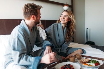 Young couple enjoying room service in bed