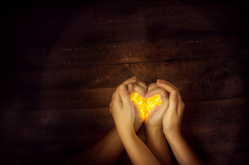 Hands of a couple making shape of a heart, holding warm Christmas lights, wooden background, top view