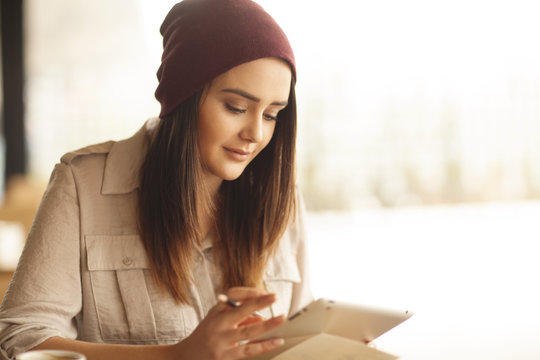 young woman reading news on her tablet