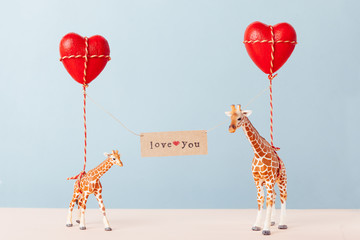 "Giraffe toys holding red heart balloons and a card spelling love you.""""iraffe toy""""""iraffe toys ho"""