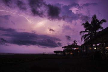 A purple sky lights up with lightning on a tropical Mexican beach