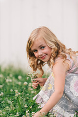 Young girl picking flowers in meadow