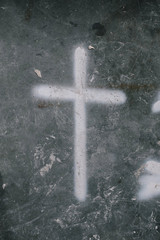Cross painted on messy concrete floor