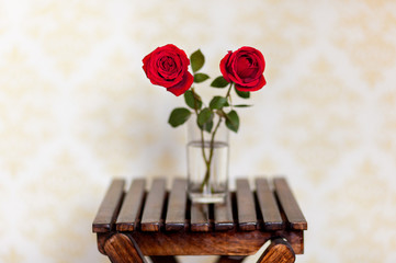 Two red roses in a glass container on a wooden stool