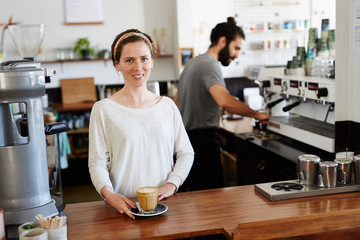 Young woman offering latte while her colleague working behind