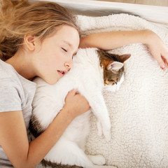 Child sleeping with cat