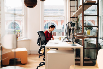 Businesswoman working on computer in office planning next business idea