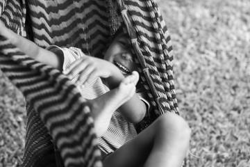 Young happy boy hiding a hammock