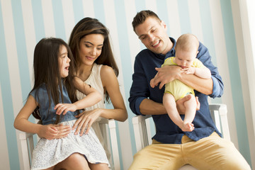 Young family with a baby sitting by the wall