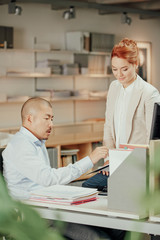 Asian businessman explains work with redhead business woman