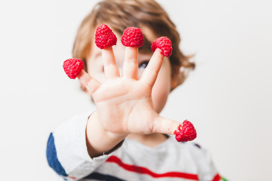 Cute Child with Raspberries on the Fingers