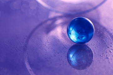 Glass blue ball on a white glass table. Abstract photo with glass and reflection. Selective focus