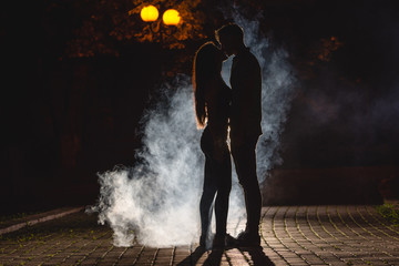 The man and woman kissing on the street on a smoke background. night time