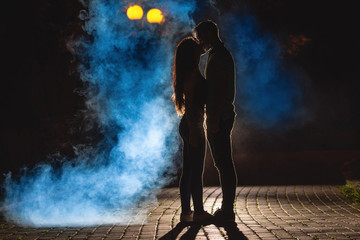 The couple kissing on the street on a smoke background. night time Fotomurales