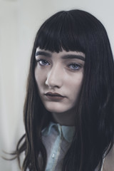Portrait of a a beautiful young girl with dark hair and blunt bangs