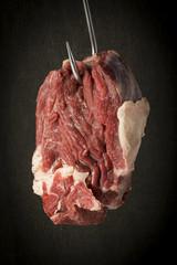 rohes Stück Rindfleisch am Haken, hängend vor dunklem Hintergrund