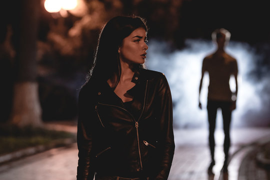 The woman stand on a dark street on a background of the man in fume. night time