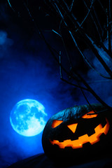 Scary Halloween pumpkin with glowing face on the background of the full moon in the fog