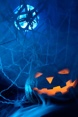 Scary Halloween pumpkin with a glowing face and a cobweb with a spider on the background of the full moon in the fog