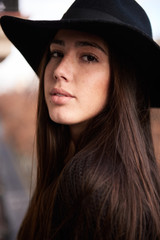 Close-up of attractive young woman in black large hat