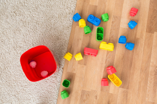 Toddler toys - rubber building blocks - scattered on the living room floor with the box next to it