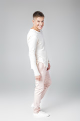 handsome young man in a white sweater and pants