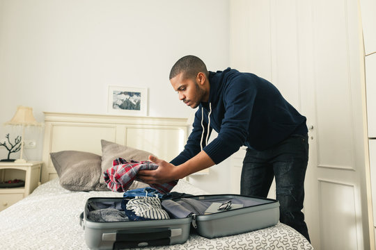 Latin man packs his suitcase for a trip.