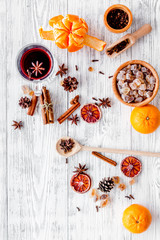 Hot mulled wine, grog cooking for new year celebration with oranges and spices ingredients on light background flat lay