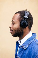Side view of an african american man listening music with headphone.