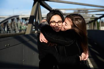 Two young girlfriends hugging on bridge