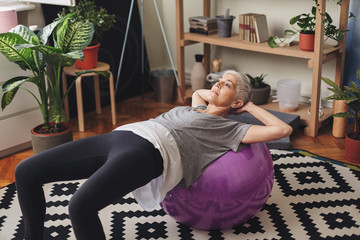 Woman exercising with a fitness ball at Home