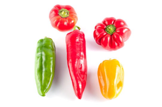 Green, red and yellow peppers on a white background